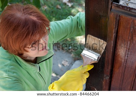 Mid adult women painting the wood