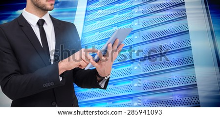 Mid section of a businessman using digital tablet pc against composite image of server tower