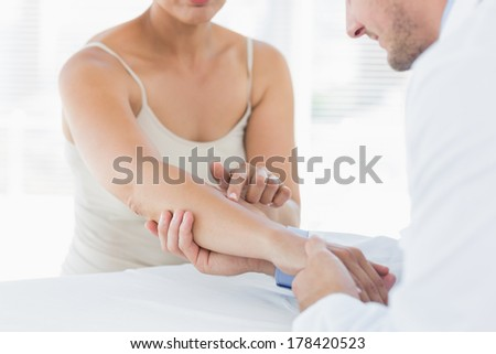 Mid section of male physiotherapist examining hand of woman in clinic