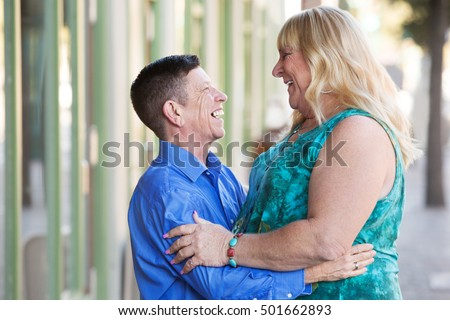 Middle aged adult transgender couple embracing outside in urban setting