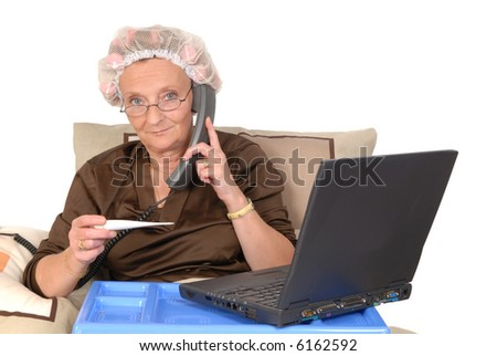 Middle aged businesswoman in bed, calling in sick, thermometer in hand, laptop on tray.  Curlers and net in hair.