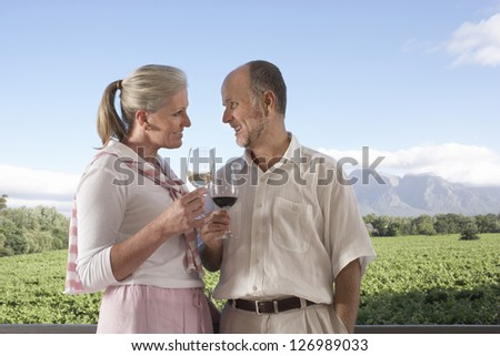 Middle aged caucasian couple with a glass of wine at vineyard