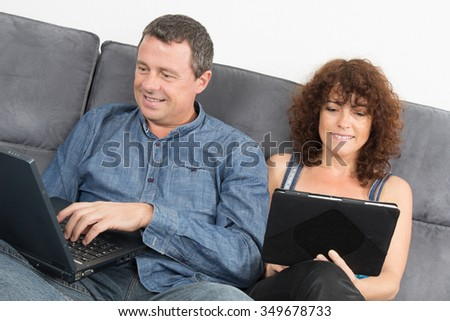 Middle aged couple on sofa at home are connected on internet