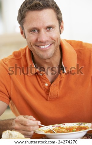 Middle Aged Man Eating Soup, Smiling At The Camera