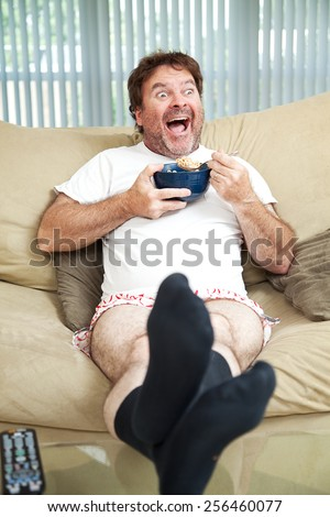 Middle-aged man in his underwea watching TV and eating cereal.  He's laughing at what's on television.