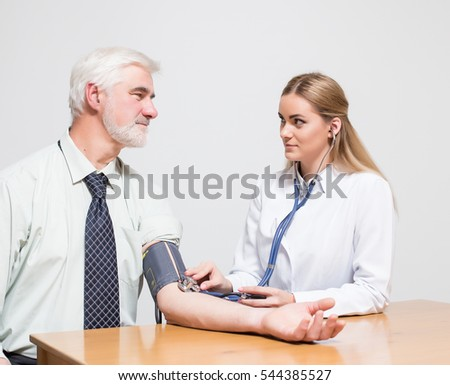 middle aged men gray hair and beard and young woman doctor listen pulse
