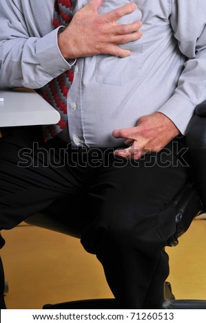 Middle aged,overweight man having a heart attack at his desk. Hand grasping his heart and pain radiating down his arm cramping his hand.