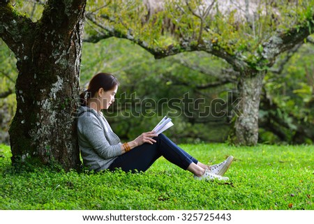 Middle aged woman sitting under a tree reading a book