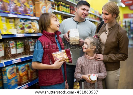 Middle-class family of four buying food in shop