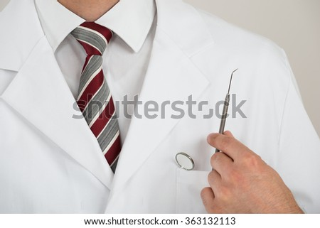 Midsection of dentist with tools in pocket against white background