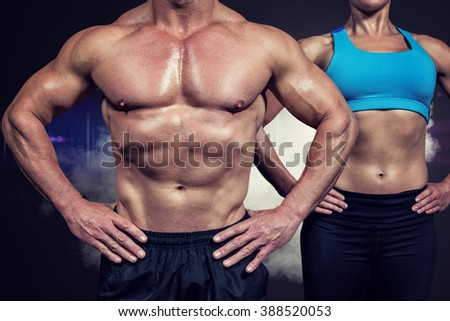 Midsection of muscular man and woman standing with hands on hip against smoke