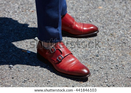 MILAN - FEBRUARY 20: Man poses for photographers with red leather shoes and blue trousers before Gucci fashion show, Milan Men's Fashion Week street style on June 20, 2016 in Milan.