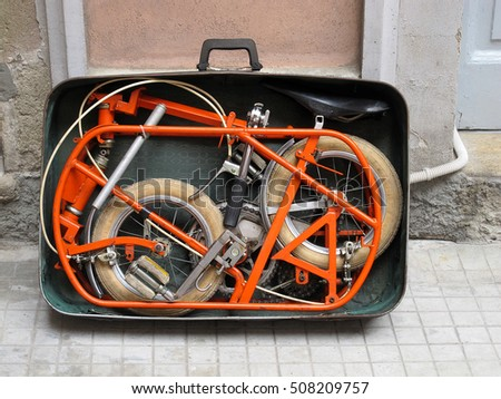 MILAN, ITALY - APRIL 2012: Orange bicycle packed up in a suitcase.