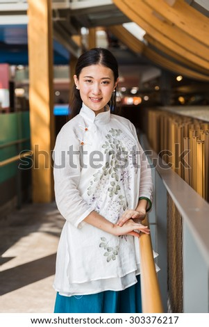 MILAN, ITALY - AUGUST 3: Beautiful Chinese girl poses outside China pavilion at Expo, universal exposition on the theme of food on AUGUST 3, 2015 in Milan.