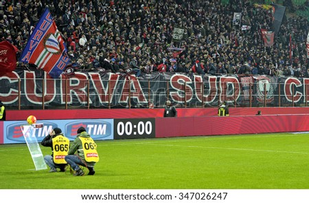 MILAN, ITALY-DECEMBER 01, 2015: Crotone soccer fans waving flags and lighting flares during the Italy Cup match at san siro stadium AC Milan vs Crotone, in Milan.