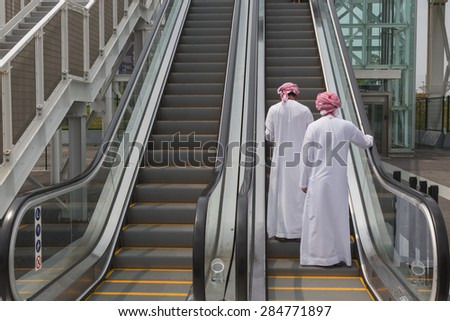 MILAN, ITALY - JUNE 1: Two arab men in their traditional clothing visit Expo, universal exposition on the theme of food on JUNE 1, 2015 in Milan.