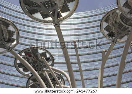 MILAN, ITALY - MAY 10 2014: Architectural detail of the glass facade on the Unicredit tower building in Milan, the tallest skyscraper in Italy. View from the bottom with a light pole in the middle