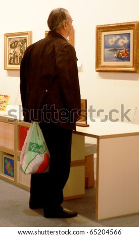 MILAN - MARCH 27: A man looks at painting during MiArt ArtNow, international exhibition of modern and contemporary art March 27, 2010 in Milan, Italy.