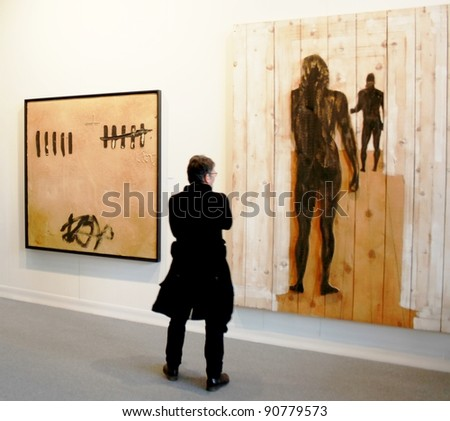 MILAN - MARCH 27: An unidentified person looks at paintings at MiArt ArtNow, international exhibition of modern and contemporary art March 27, 2010 in Milan, Italy.
