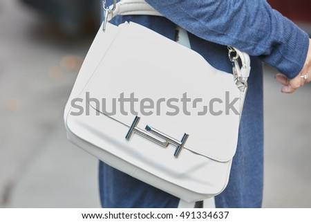 MILAN - SEPTEMBER 21: Woman with white leather Tod's bag before Gucci fashion show, Milan Fashion Week street style on September 21, 2016 in Milan.