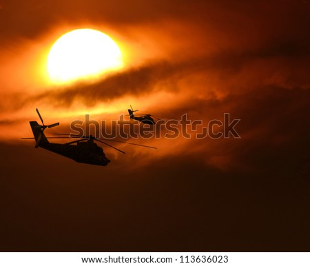 Military helicopters silhouette flying against sun