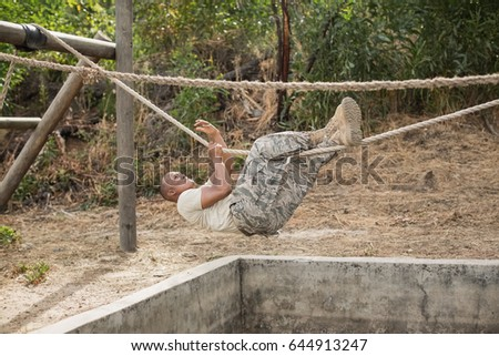 military soldier climbing rope during obstacle course training at boot camp military soldiers climbing rope during obstacle stock photo      rh   shutterstock