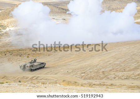 MILITARY TRAINING ZONE, ISRAEL - JUNE 17, 2015: Israel army Armored Personnel Carrier charging enemy targets through a smoke screen. Israeli military armored vehicle attacking terror objectives.
