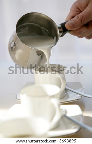 milk being poured into white coffee cup from metal pot