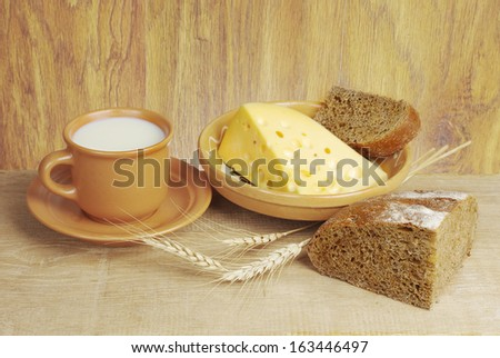 Milk, bread and cheese. Wooden background
