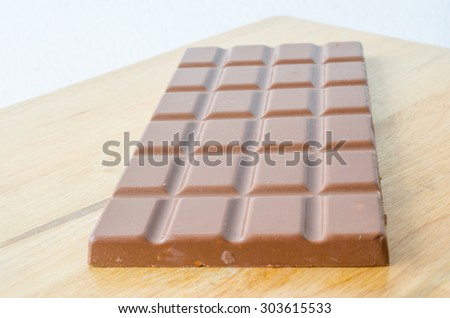 Milk chocolate bar on wooden table