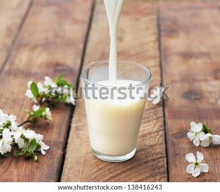 milk is flowing down to glass on wooden table