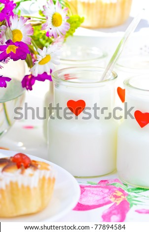 milk yogurt in a glass jar, rolls with cherry and cinnamon and a garden flowers