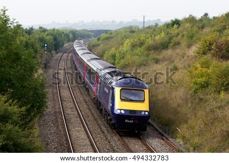 MINETY, UK - SEPTEMBER 25: A First Great Western express train passes an opencast landfill site on September 25, 2013 in Minety. FGW operate at 208 stations over an operating distance of 2130 km