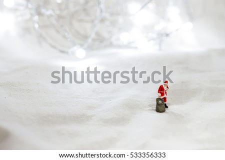 Mini Figure Santa Claus with Gift Bag stand alone in winter snow minimal scenery