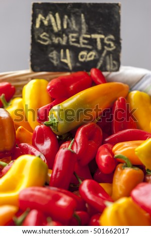 Mini sweet bell peppers on display at a market.