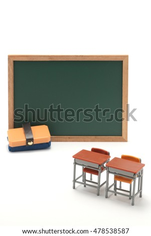 Miniature blackboard and school desks on white background.