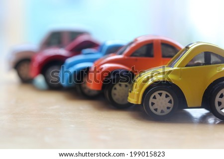 miniature colorful cars standing in line showroom sale concept. Different colored cars - blue, yellow, orange, white and red color cars standing next to each other - car agent sale concept