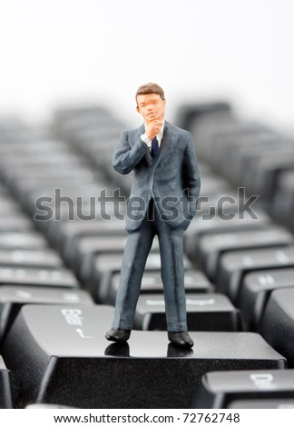 Miniature figurine of successful businessman standing on computer keyboard