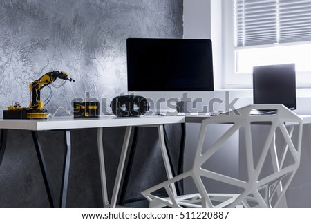 Minimalistic chair and desk with robot located close to the window in grey room interior