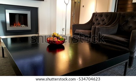Minimalistic interior design with a big black table with fruit bowl and comfortable arm chairs in front of a fireplace located in a lounge