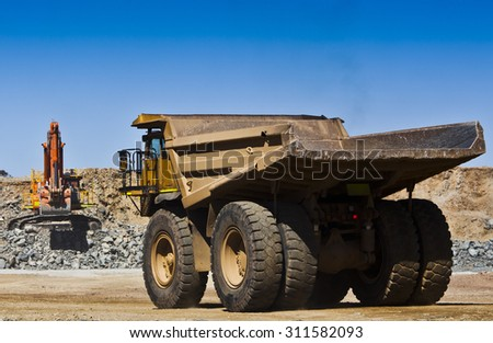 Mining scene. Large truck drives towards digger to fill with ore from open cast mine. All logos removed.