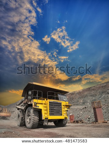 Mining truck loaded with iron ore driving along the opencast on sunset