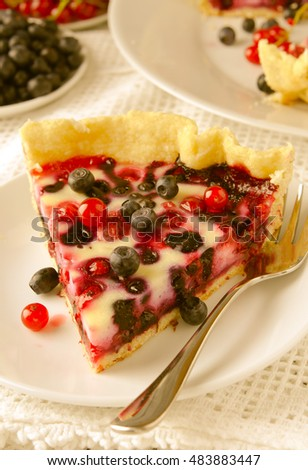 Mix berry tart, pie, cake with raspberries, bilberries, bluberries, red currant and cream on white background