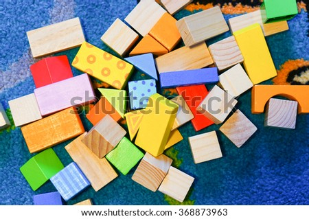Mix of wooden toy blocks on blue carpet