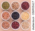 Mixed beans and lentils in the white bowl  on brown background. mung bean, groundnut, soybean, red kidney bean , black bean ,red bean,green bean,millet and brown pinto beans . - stock photo