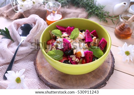 Mixed fruit with yoghurt and granola topped with honey served in a bowl on wooden background.