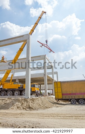 Mobile crane is carry concrete joist to assembly huge hall.