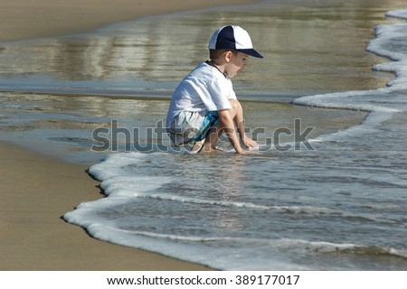 Model released image of young preschool boy playing in the waves at the beach. Wearing white shirt, blue and white hat and patterned blue and white shorts. Tongue sticking out in concentration