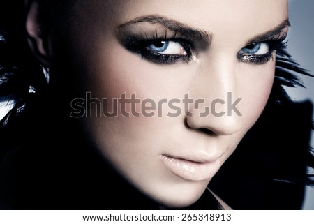 Model with silver glitter makeup wearing tiara.