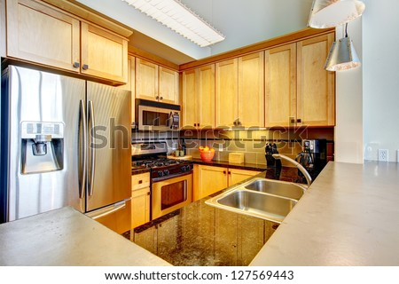 Modern apartment wood kitchen interior with large counter top.